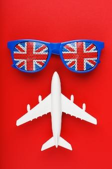 Un avion de passagers blanc vole en lunettes de soleil avec le drapeau du royaume-uni ,.