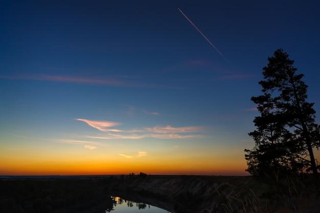 Avion de passagers dans le ciel nocturne. les nuages se reflètent dans l'eau de la rivière