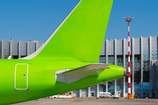 Avion de passagers vert à l'aéroport par beau temps