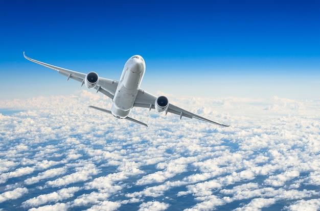 L'avion de passagers vole à un niveau de vol sur fond de nuages et de ciel bleu.
