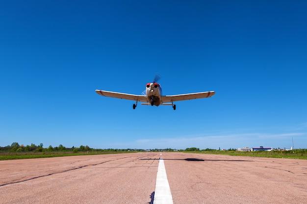 L'avion piper cherokee à basse altitude survole la piste. un petit aérodrome privé avec différents avions. aviation privée