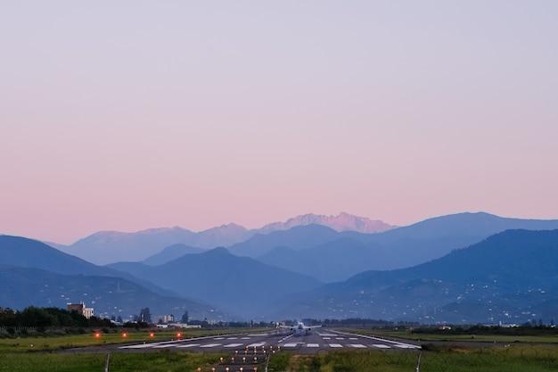 Avion sur la piste sur fond de montagnes
