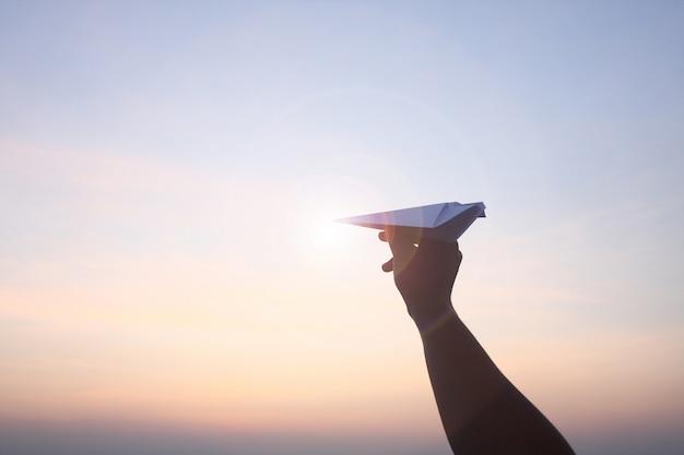 Avion pliant en papier mobile dans le ciel du matin.