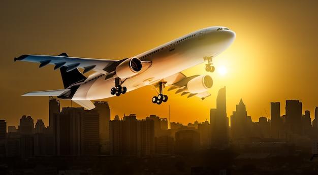 Avion pour le transport survolant la ville sur fond magnifique coucher de soleil