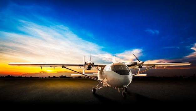 Avion de stationnement à la piste d'aéroport sur le beau fond de coucher du soleil