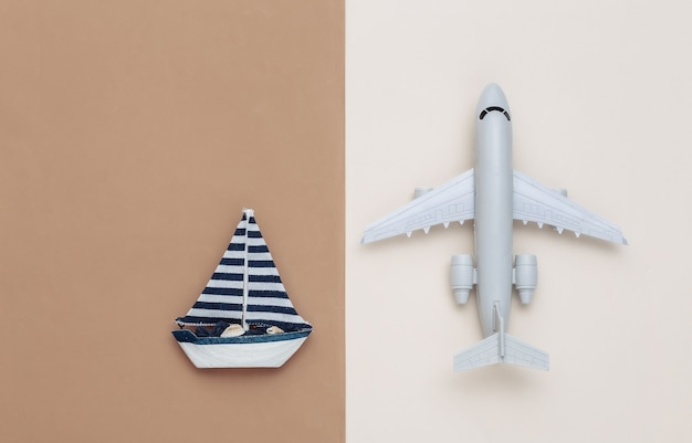Avion et voilier sur fond beige marron. vue de dessus