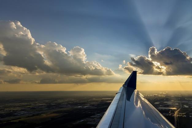 Avion de vol d'aile au-dessus des nuages blancs pelucheux dramatiques sur le ciel bleu pendant le coucher du soleil