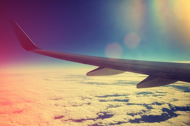 Avion volant au-dessus des nuages au lever du soleil