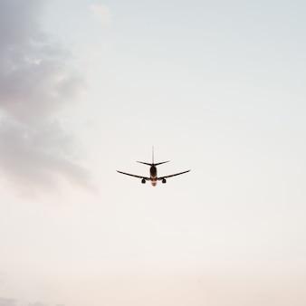 Avion volant dans le ciel au coucher du soleil avec des nuages violets roses