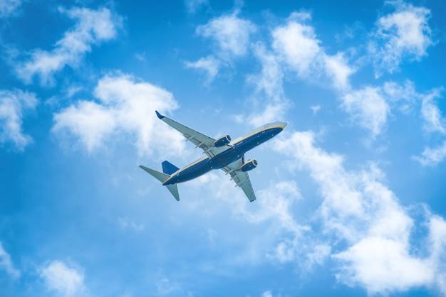 Un avion volant dans le ciel bleu avec des nuages blancs