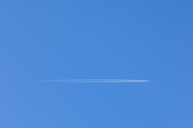 Avion volant à travers le ciel bleu clair, avec un sentier derrière.