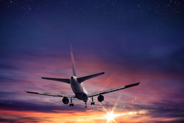 L'avion vole dans le ciel au coucher du soleil