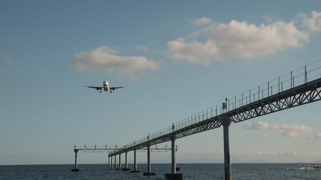 Un avion vole dans un ciel bleu vif au-dessus de la mer calme. il survole un grand pipeline encadré debout dans l'eau