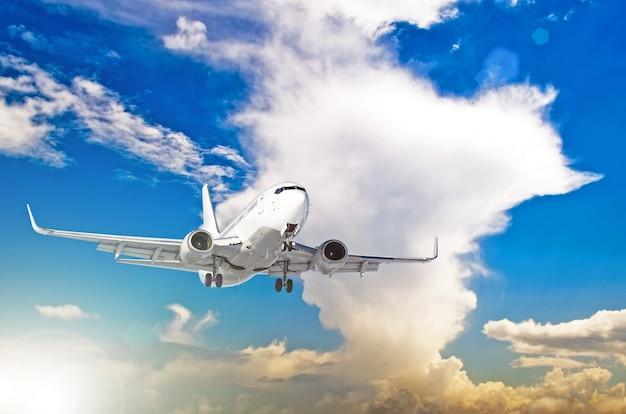 Avion à voler sur le ciel avec coucher de soleil de cumulus.