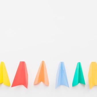 Avions en papier coloré dans la rangée