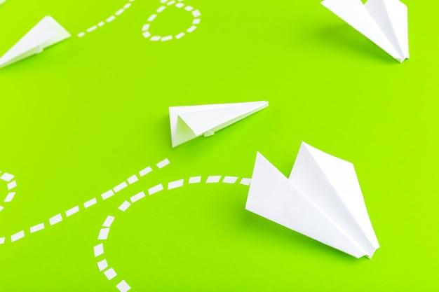 Avions en papier connectés avec des lignes pointillées sur fond vert. concept commercial