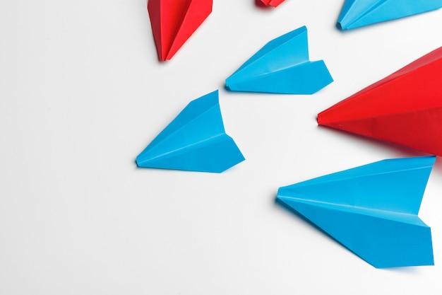 Avions en papier rouge et bleu sur blanc. leadership et compétition commerciale