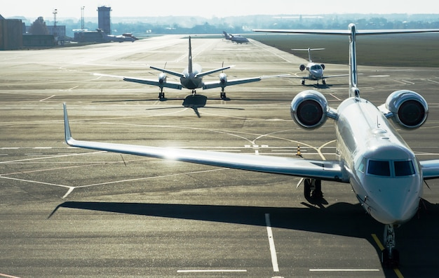 Des avions à réaction privés se tiennent sur la ligne d'atterrissage.