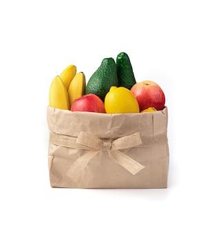 Avocat, bananes, pommes et citrons dans un sac avec un arc sur fond blanc.