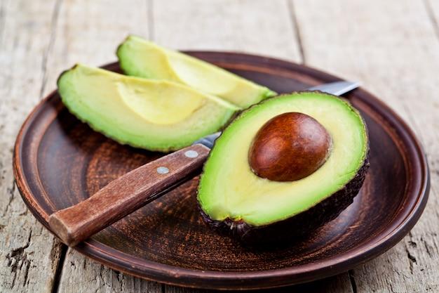 Avocat bio frais sur une assiette en céramique et un couteau sur une table en bois rustique
