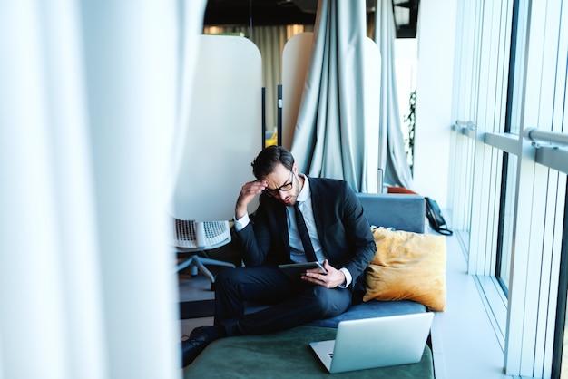 Avocat caucasien inquiet à l'aide de tablette alors qu'il était assis dans le bureau sur un canapé. à côté de lui un ordinateur portable.