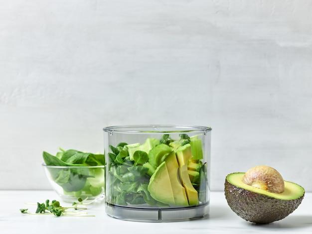 Avocat, céleri et épinards dans un récipient en plastique transparent pour préparer un smoothie au petit-déjeuner sain sur la table de la cuisine
