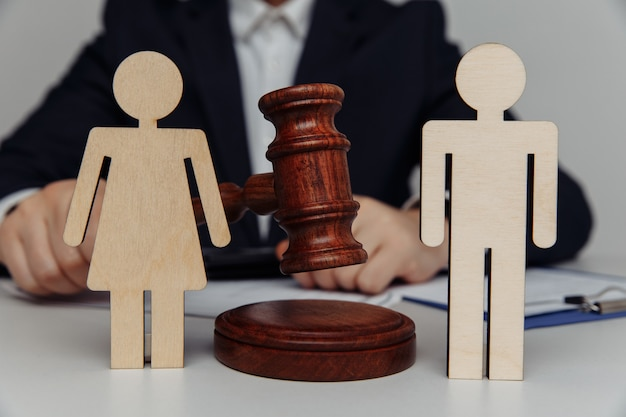 Un avocat ou un conseiller tient le marteau derrière des figures de la jeune famille, du divorce et du concept de droit.