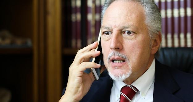 Un avocat contrarié parlant au téléphone dans son studio