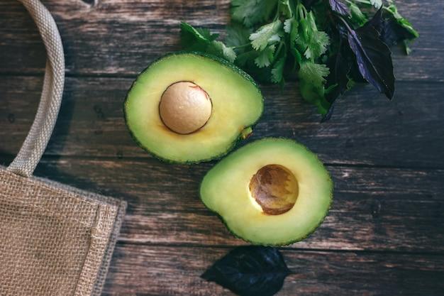 Avocat coupé en deux sur une table en bois, coriandre et basilic à côté d'un sac de paille. concept de nutrition adéquate et saine, végétarisme.