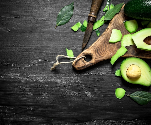 Avocat et couteau sur la planche. sur un fond en bois noir.