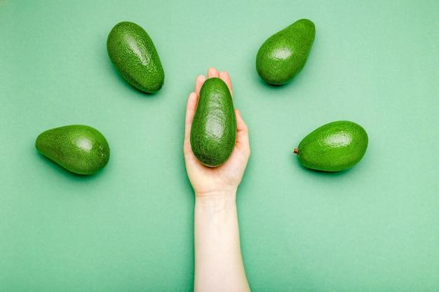 Avocat dans la main féminine sur la couleur verte pose plate minimale
