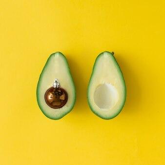 Avocat et décoration de boule de noël sur fond jaune vif. concept de noël. mise à plat.