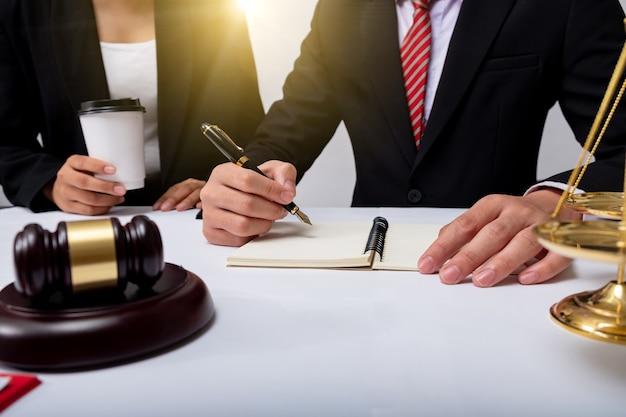 Avocat détail d'un juge assis à son bureau, étudiant de nouvelles lois et législations et prenant des notes. mise au point sélective.