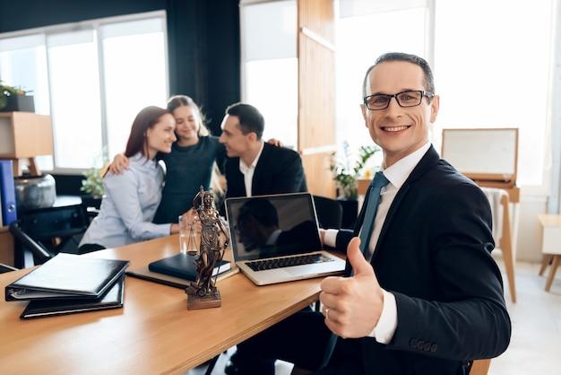 Un avocat en droit de la famille montre son pouce assis à table.
