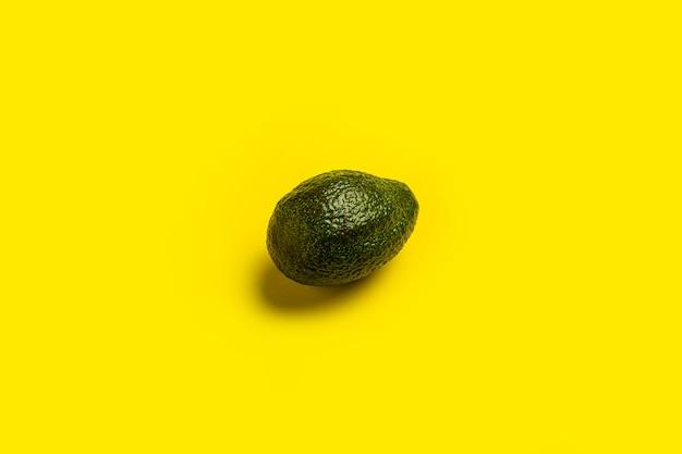 Avocat entier frais mûr vert foncé sur un jaune vif