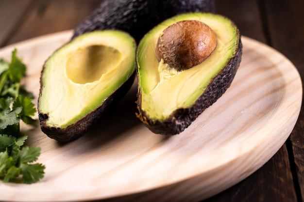 Avocat fendu en deux sur du bois. nourriture saine et végétarienne