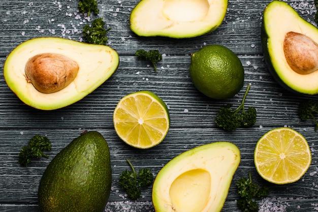 Avocat frais, citron vert, persil et sel sur fond de bois bleu ancien