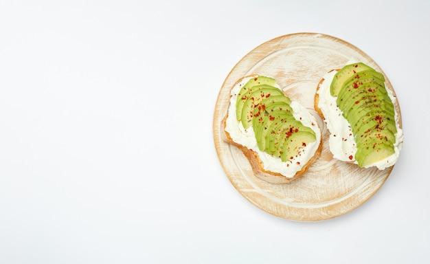 Avocat frais tranché sur des toasts de pain de blé