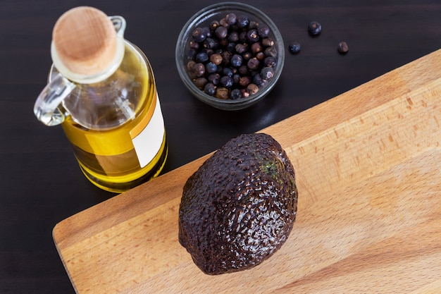 Avocat haas mûr sur planche à découper et huile d'avocat prête à cuire.