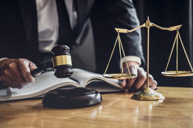 Avocat ou juge travaillant avec des documents contractuels, des documents, un marteau et des balances de justice
