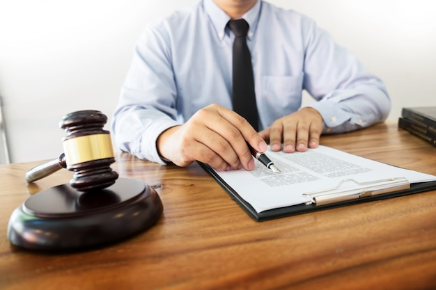 Avocat main écrit le document au tribunal (justice, droit) avec son bloc.