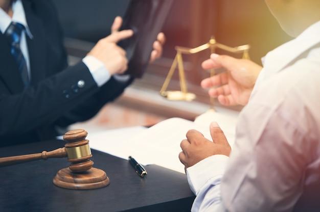 L'avocat parlant et le conseiller juridique décisionnel présente au client un contrat signé avec le juge gavel