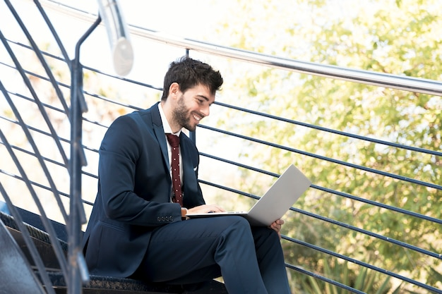 Avocat smiley vue de côté travaillant sur ordinateur portable
