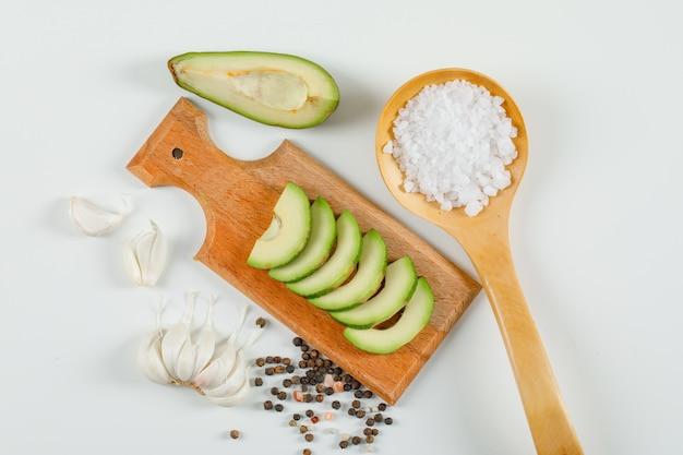 Avocat en tranches dans une planche à découper avec des cristaux de sel dans une cuillère en bois, des gousses d'ail et des grains de poivre vue de dessus sur une surface blanche
