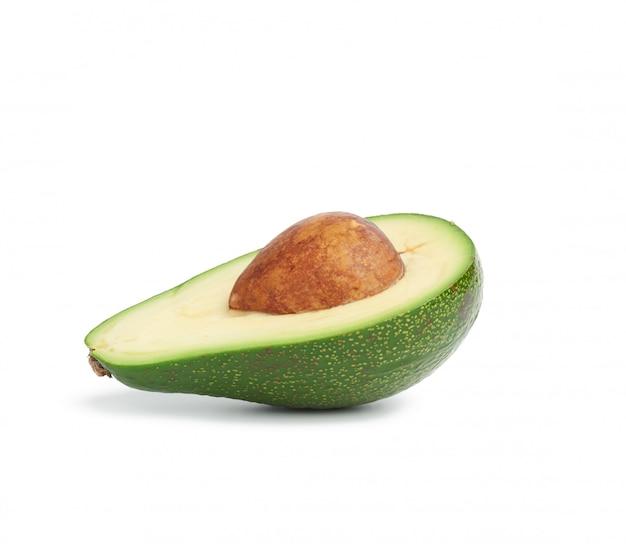 Avocat vert à moitié mûr avec un noyau brun isolé