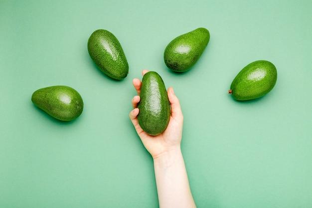 Avocat vert organique mûr frais dans la main femelle