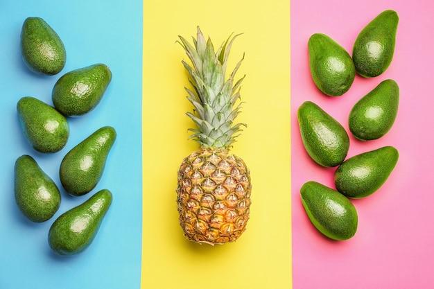 Avocats et ananas frais sur papier multicolore