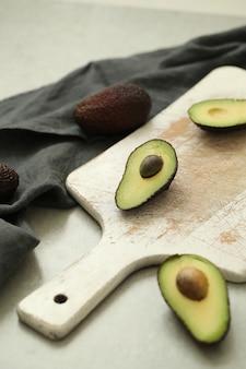 Avocats entiers et coupés sur une planche à découper en bois