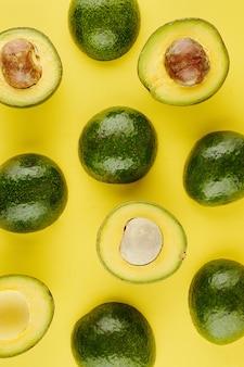 Avocats frais coupés et non coupés mûrs sur fond jaune vif, vue du haut