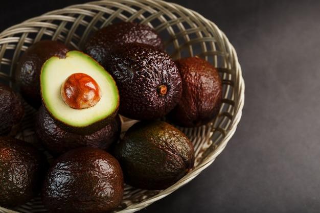 Avocats mûrs dans un panier sur une table noire, avec un fruit coupé et une pierre. espace libre, vue de dessus